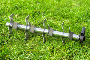Aerating steel roller on the green grass battling lawn moss